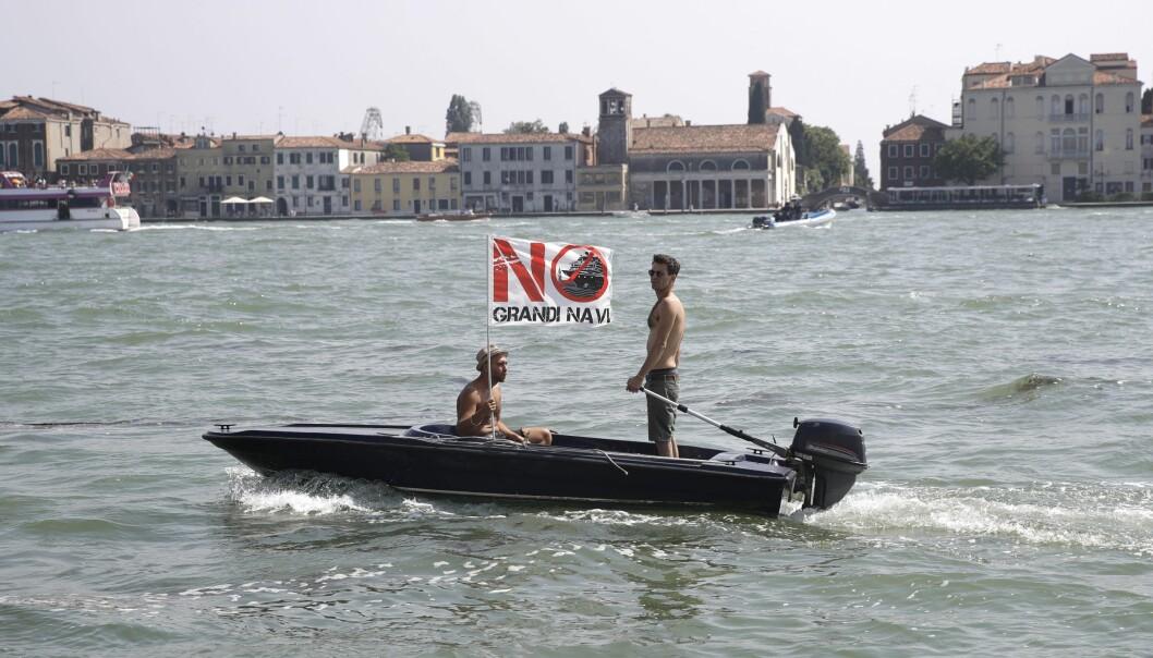 Aktivister protesterar mot kryssningsfartyg utanför Venedig i juni 2019 med en flagga med orden Inga stora fartyg på itelienska.