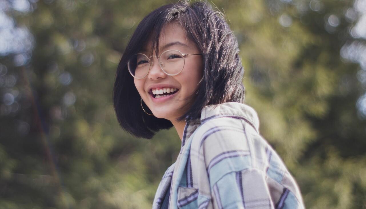Kvinna ler mot kameran. I bakgrundens syns ett grönområde.