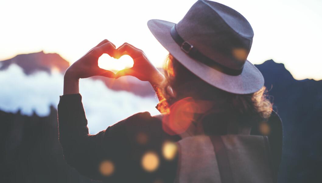 Kvinna formar ett hjärta med sina händer.