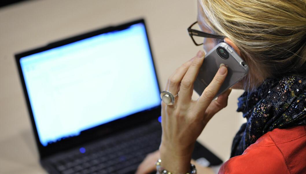 Kvinna sitter framför en dator och pratar i telefon.