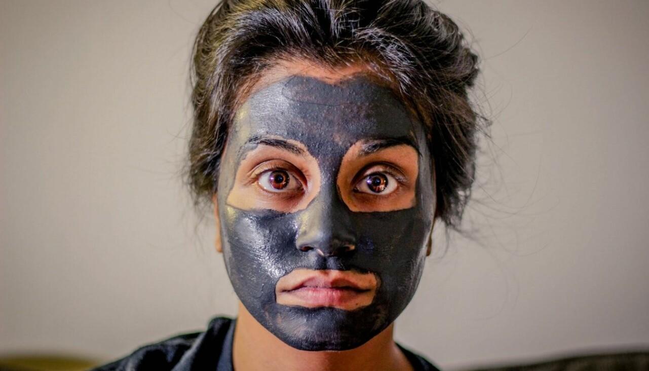 En kvinna med en mörkgrå ansiktsmask tittar in i kameran