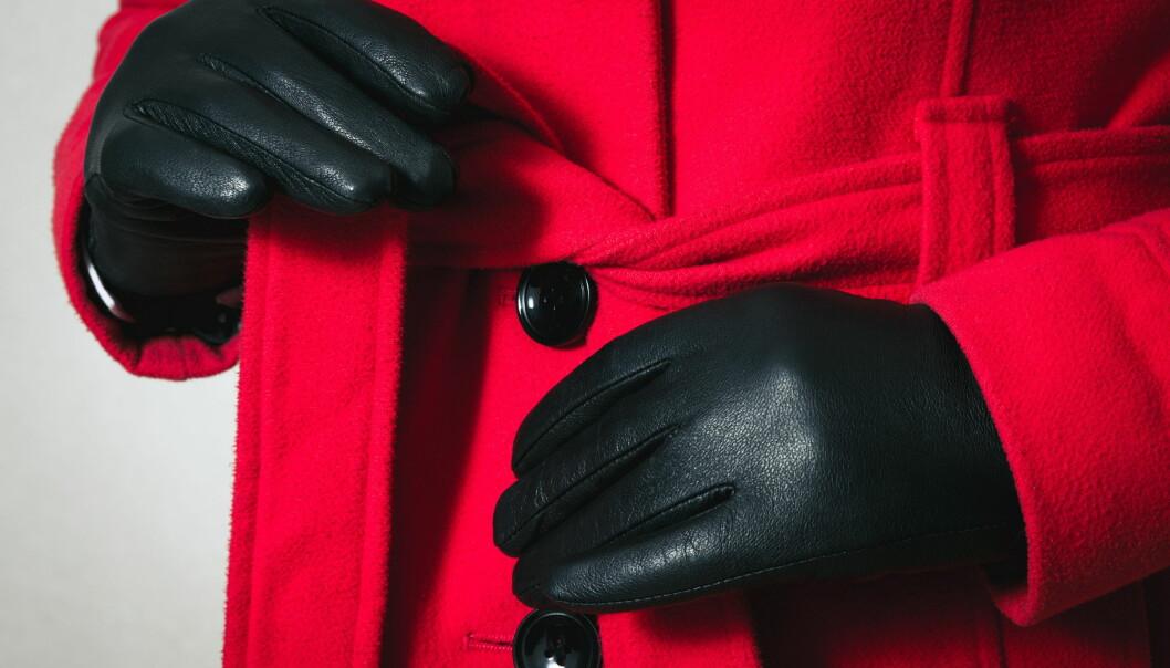 Kvinna i handskar knyter en kappa med skärp och knappar.