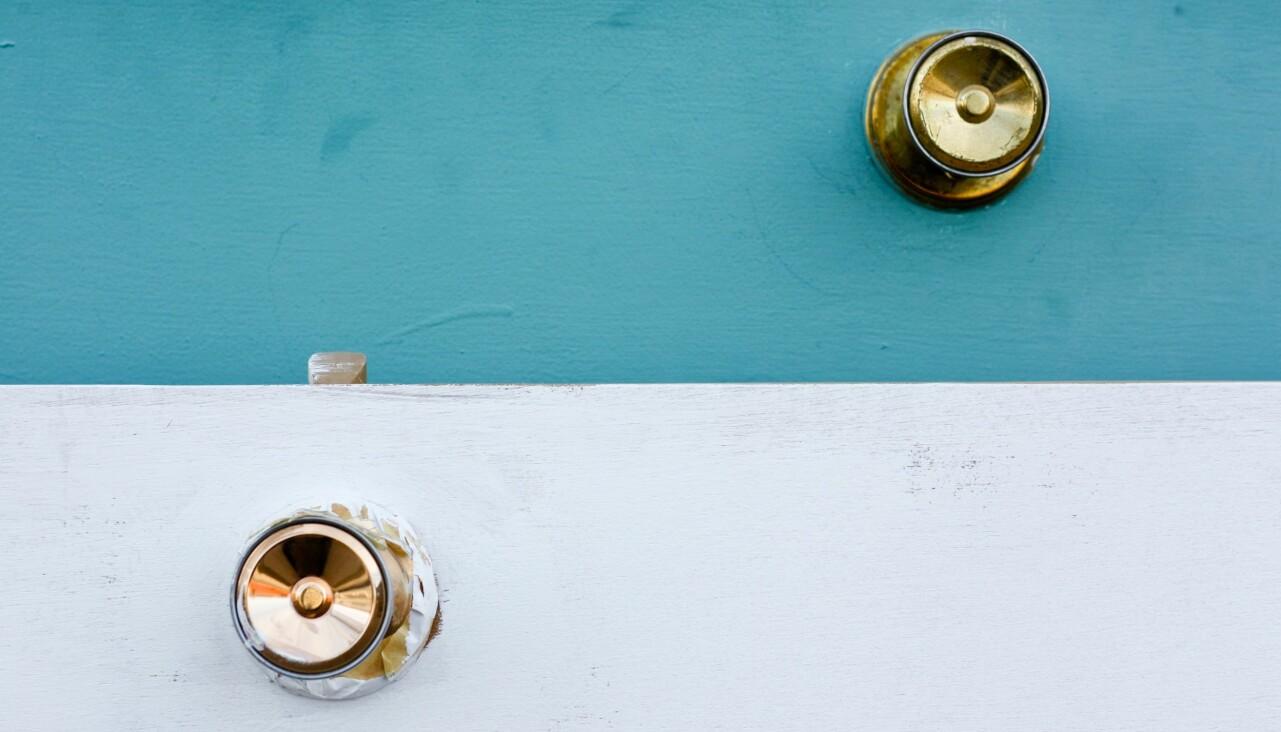 Två blanka dörrhandtag sitter på en turkos och en vit dörr