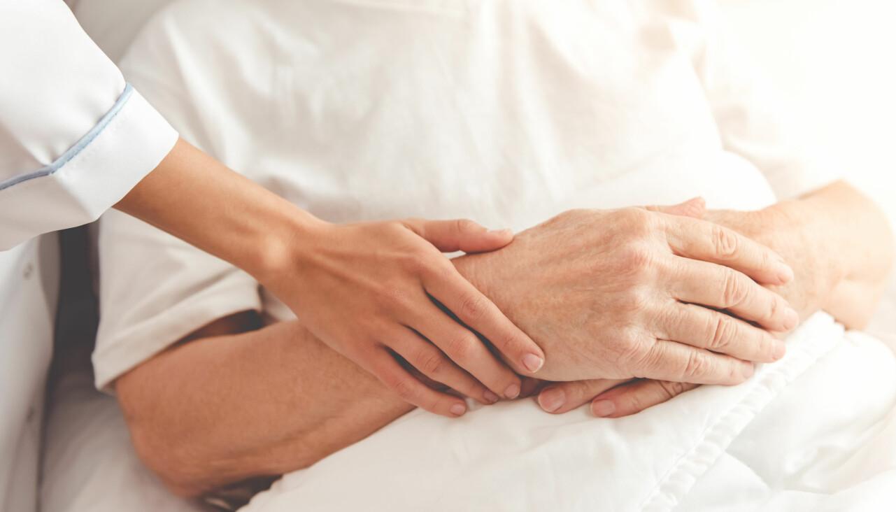 Sjuksköterska håller handen på en äldre patient.