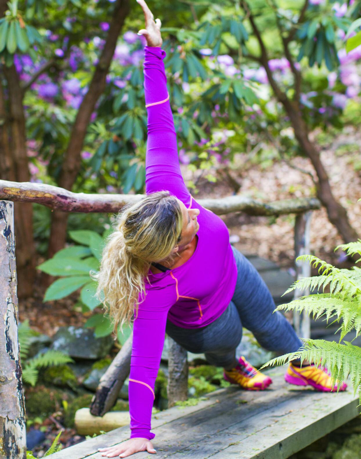 Josefin Liljegren i träningskläder står i sidoplanka utomhus.