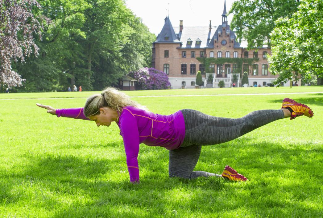 Kvinna gör en träningsövning på gräsmatta framför Sofiero slott.