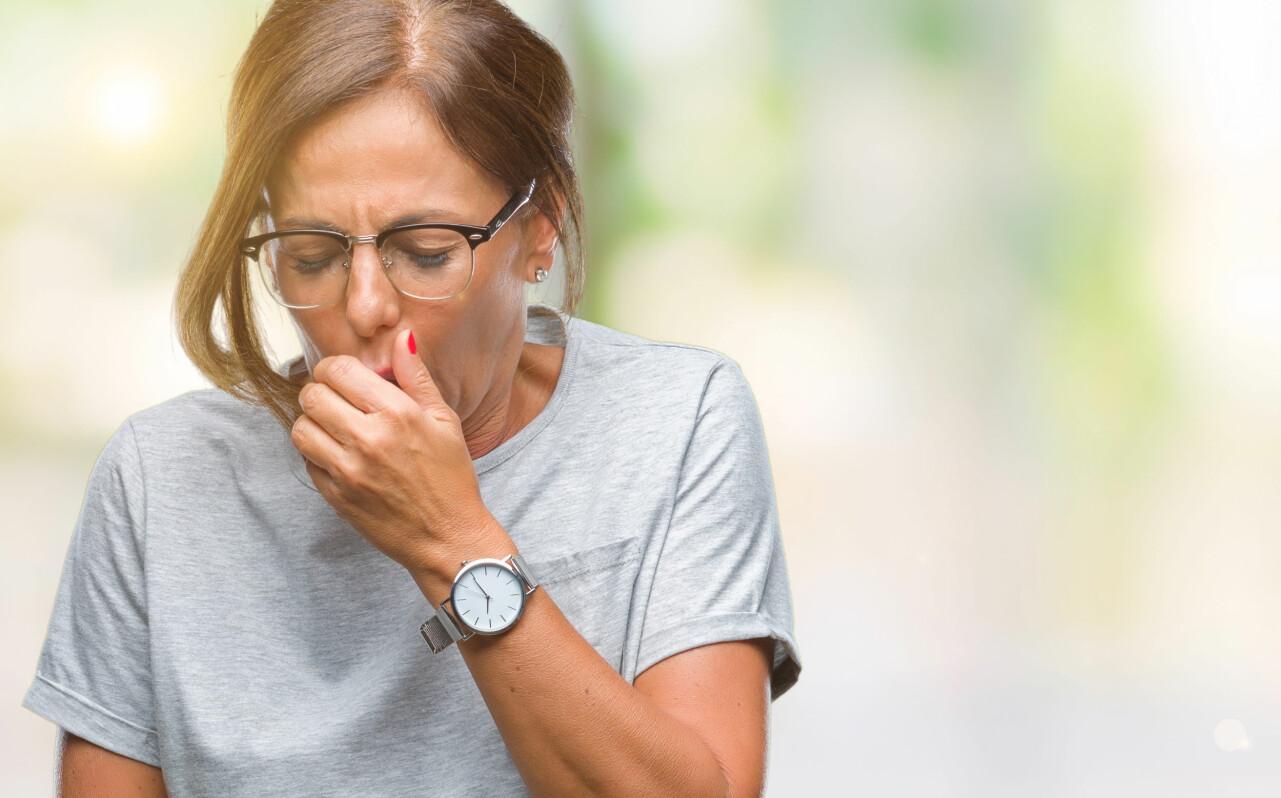 Kvinna hostar med handen för munnen.