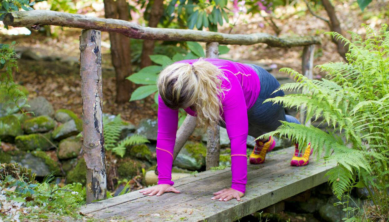 Josefin Liljegren står i plankposition på en träbro.