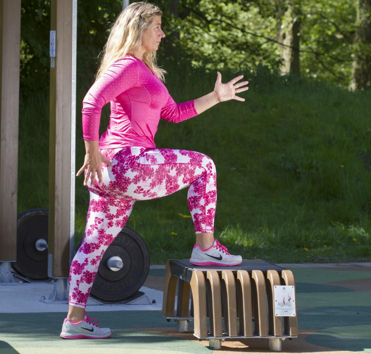 Josefin Liljegren visar step-ups på ett utegym.