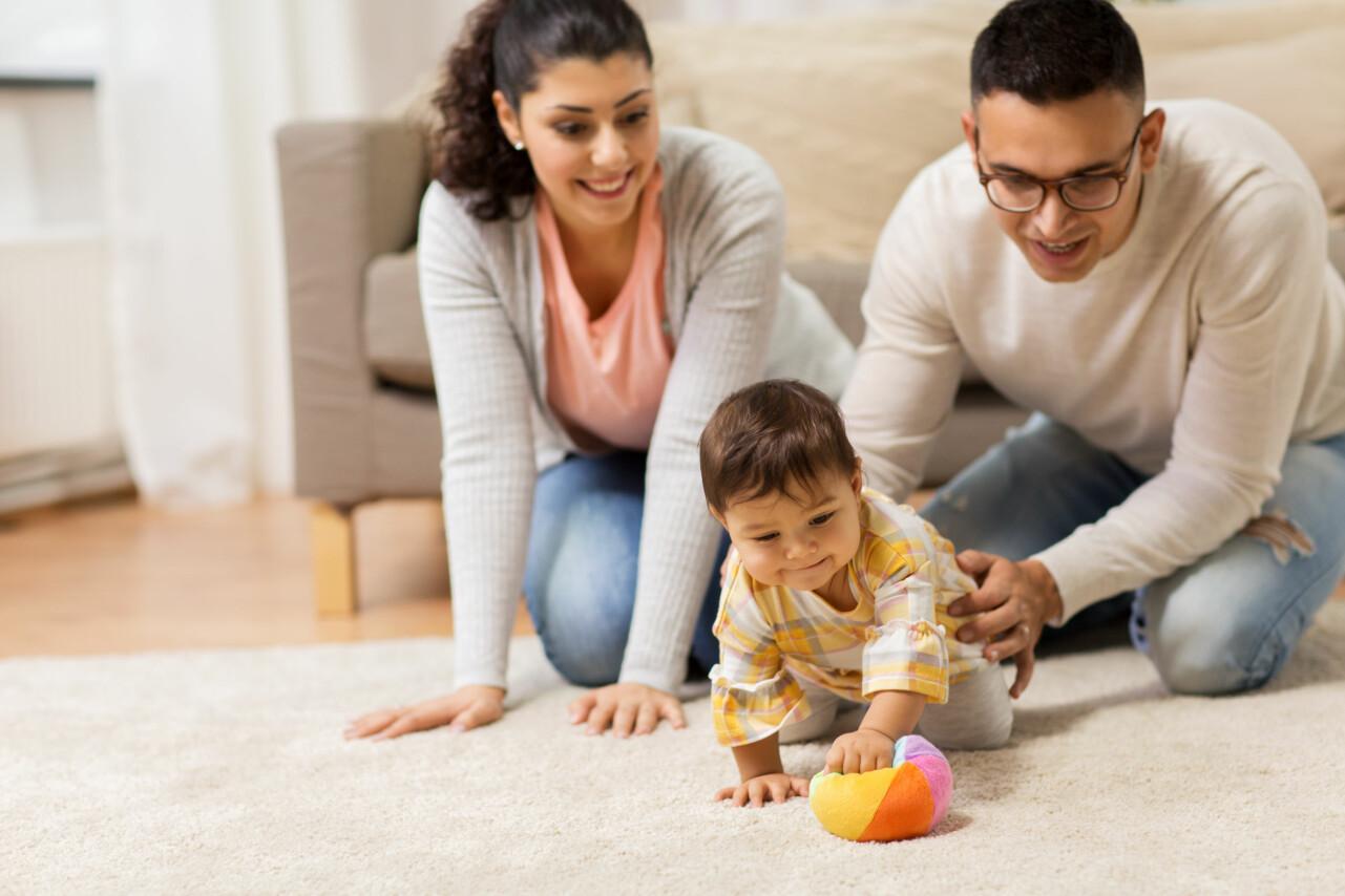 Föräldrar leker med ett barn på golvet.
