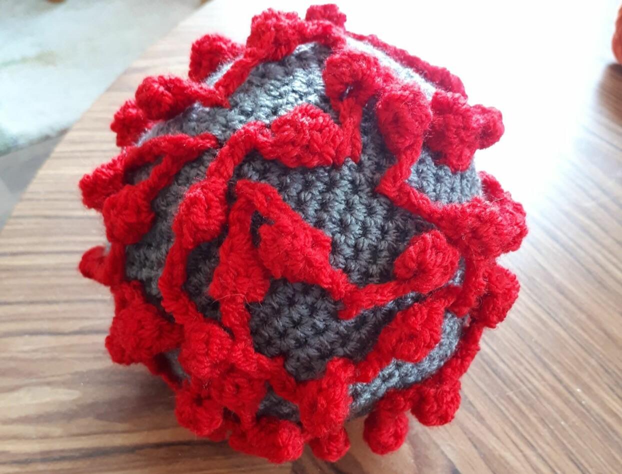 Pedagosgisk virkade grå boll med fastsatta röda trådar som ser ut som ett coronavirus.