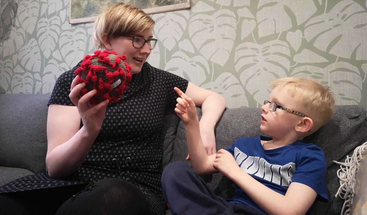 Emma Heldt sitter tillsammans med sonen Sixten i familjens soffa och visar upp sin hemvirkade coronaboll Virkus.