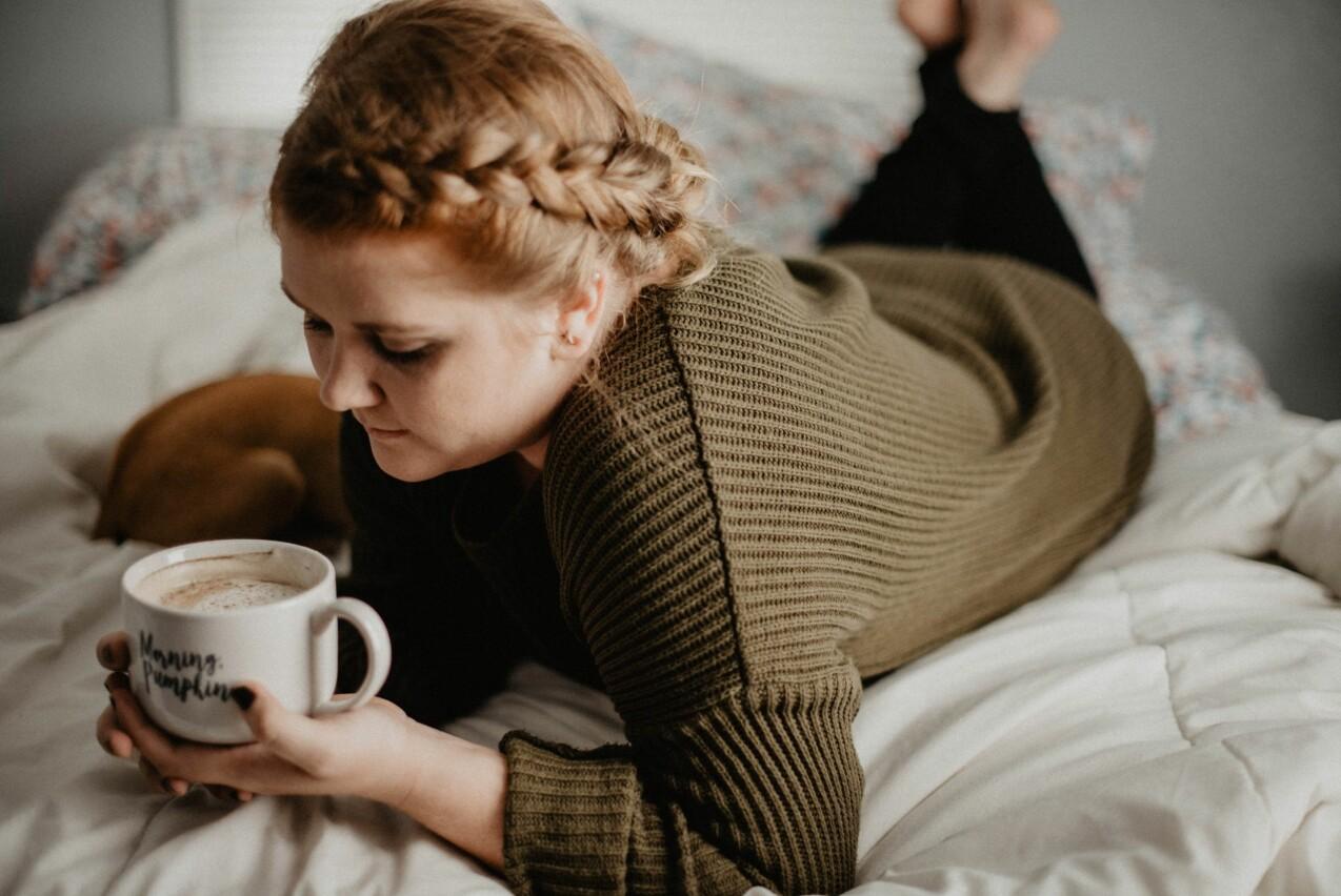 Kvinna ligger i en säng och håller en kopp kaffe i händerna.