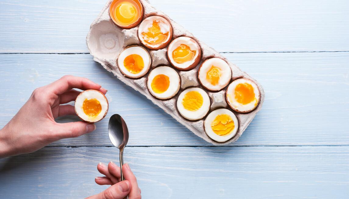 Kartong med tio kokta ägg med krämiga gulor, en kvinnohand och en sked.