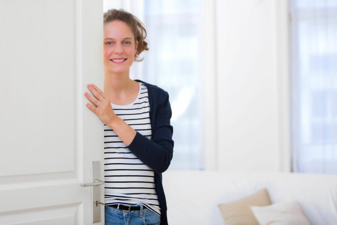 Kvinna öppnar dörren för en besökare.