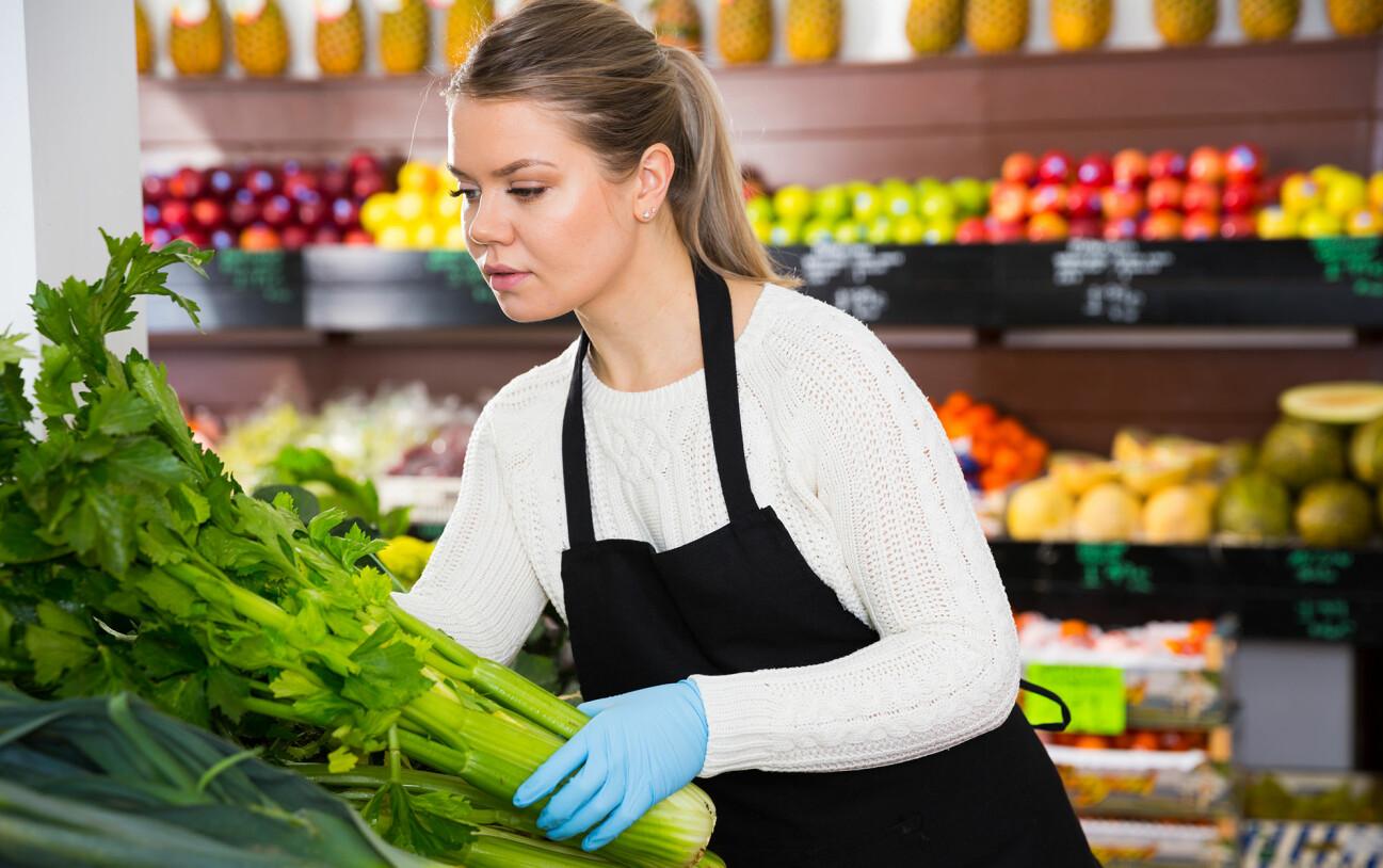 Kvinna i handskar handlar och försöker att undvika coronasmitta.