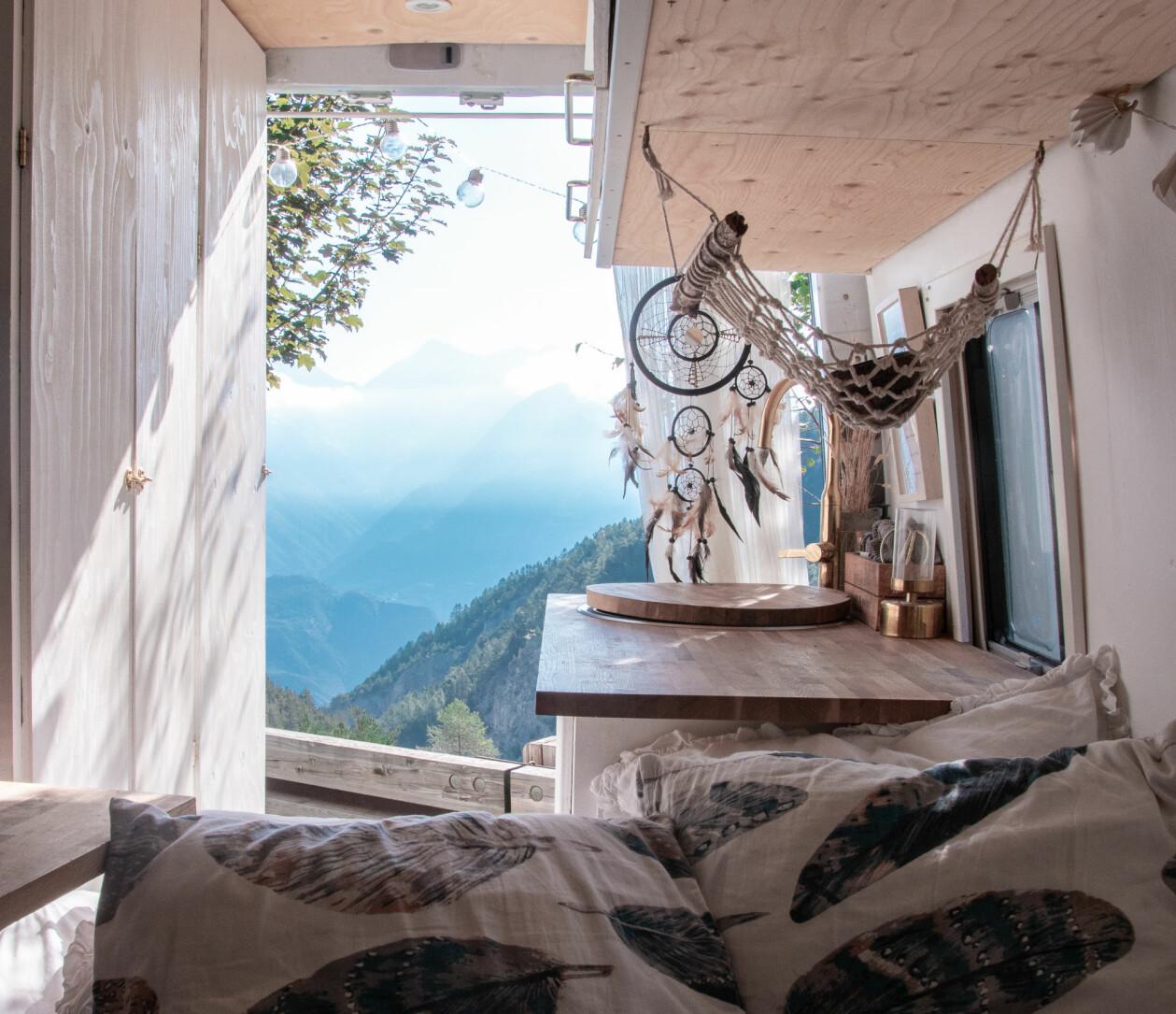 Utsikt från Sandras säng. Den öppna baklucka på biler vätter mot bergstoppar och dalar, beslöjade av dimmiga moln.