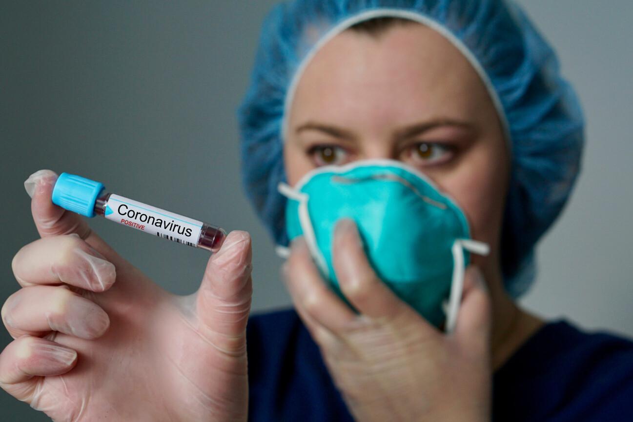 Kvinna med munskydd håller ett provrör med blod.