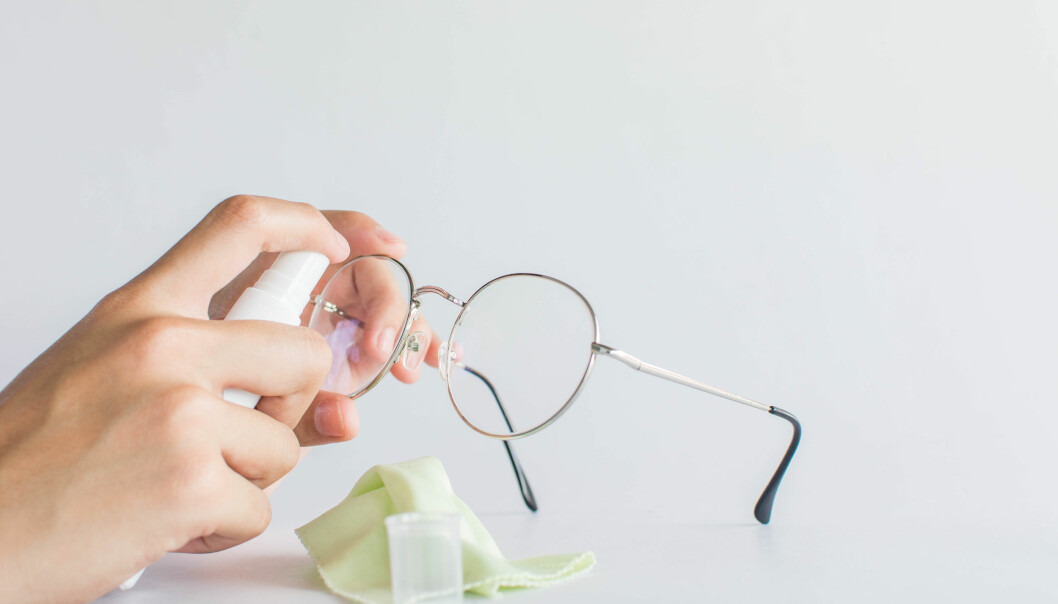 Sprayar glasögon med rengöringsspray.