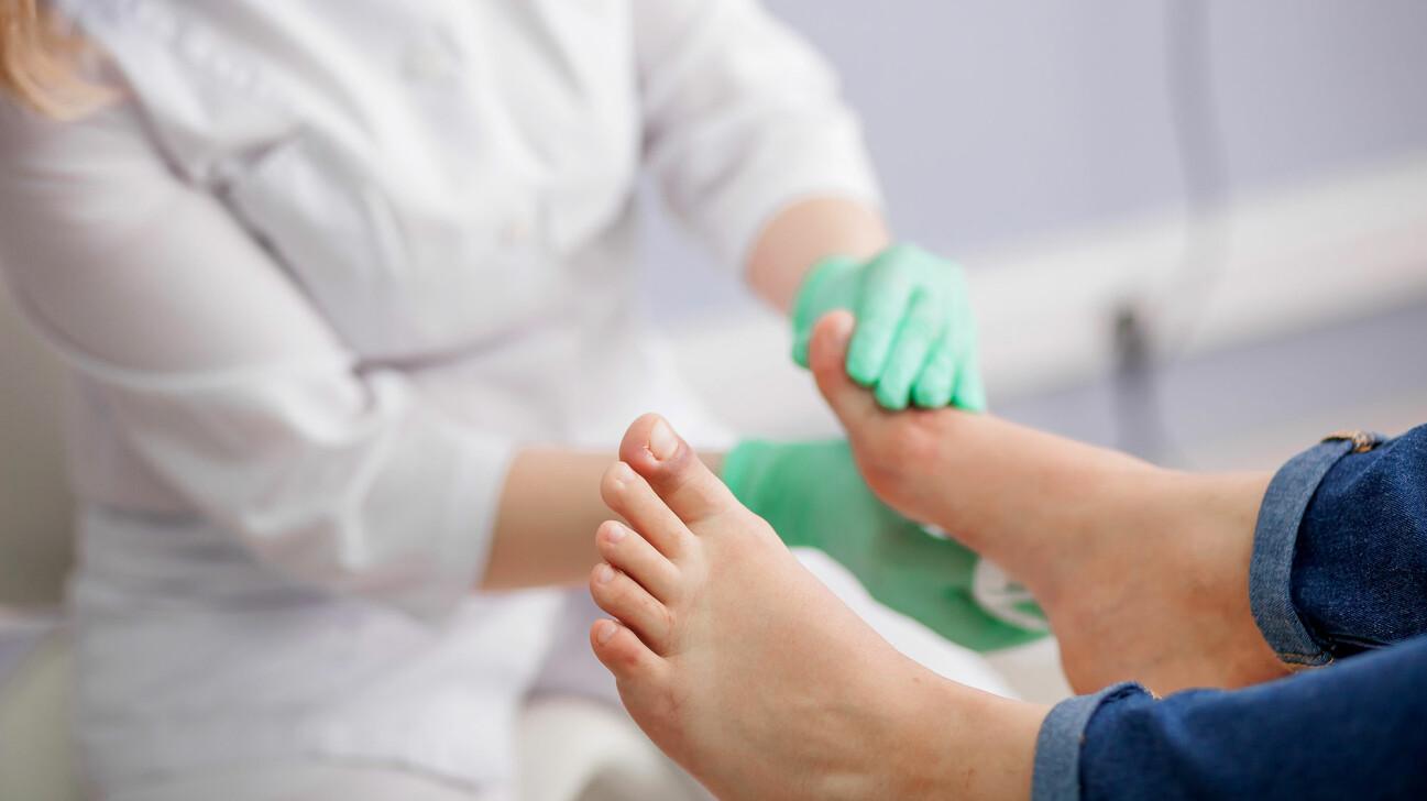 Läkare undersöker en persons fötter.