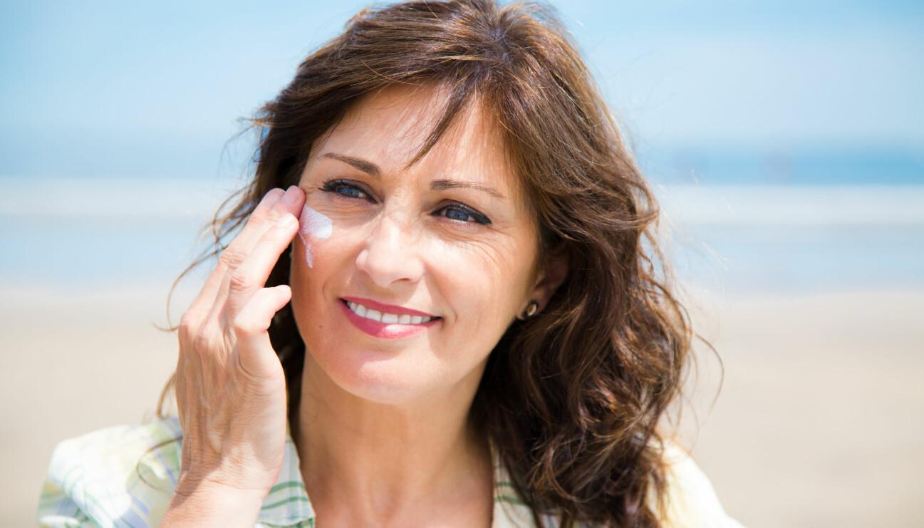 En kvinna applicerar solskydd.