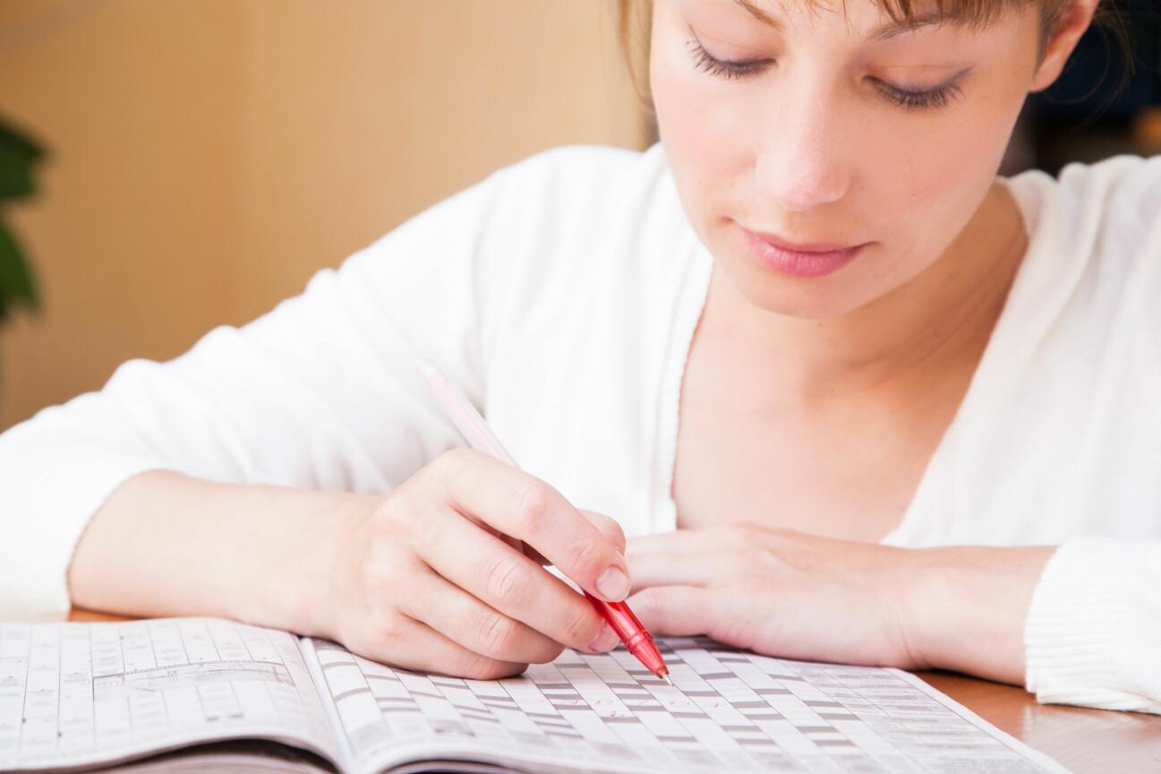 Kvinna löser korsord i en tidning.