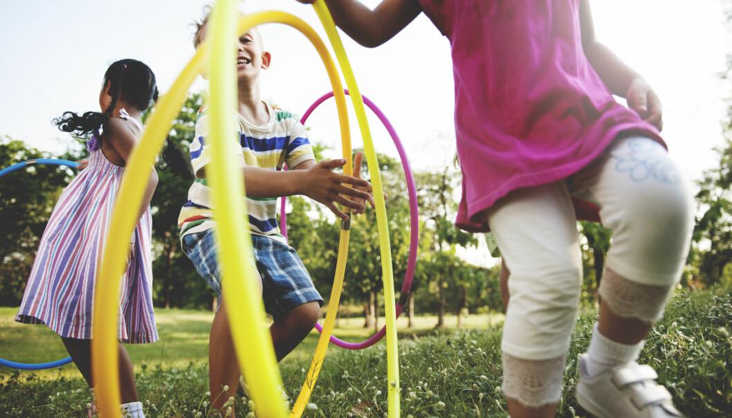Barn leker med rockringar på en äng.