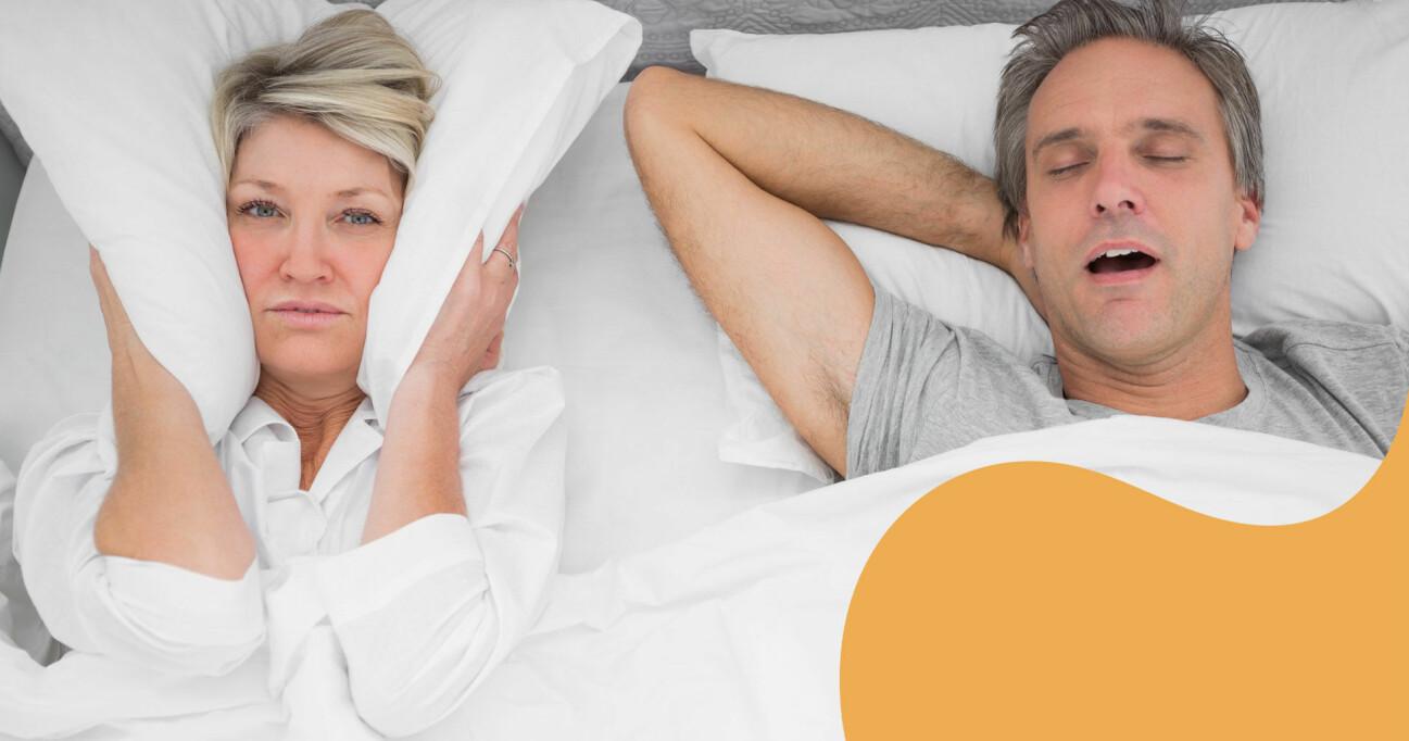 Kvinna håller kudde för huvudet när mannen snarkar.