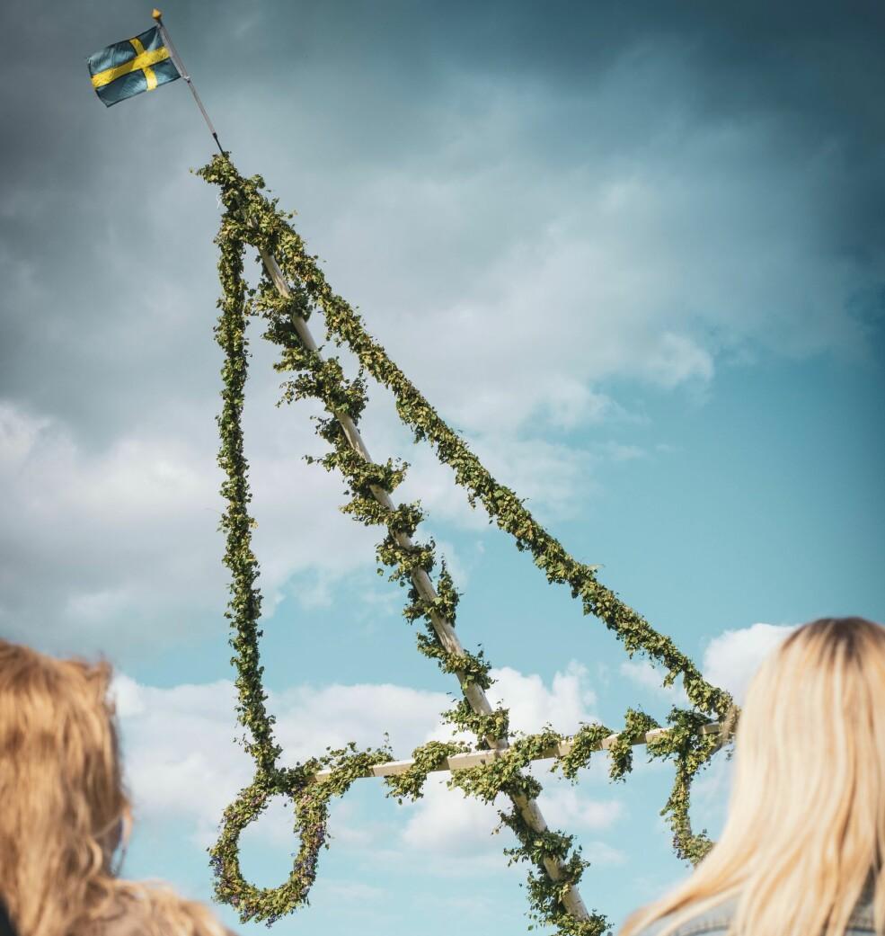 En midsommarstång med en svensk flagga i toppen.
