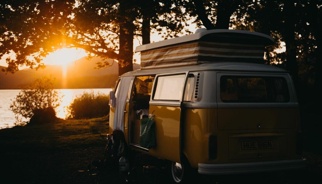 En husbil i en solnedgång vid en sjö.