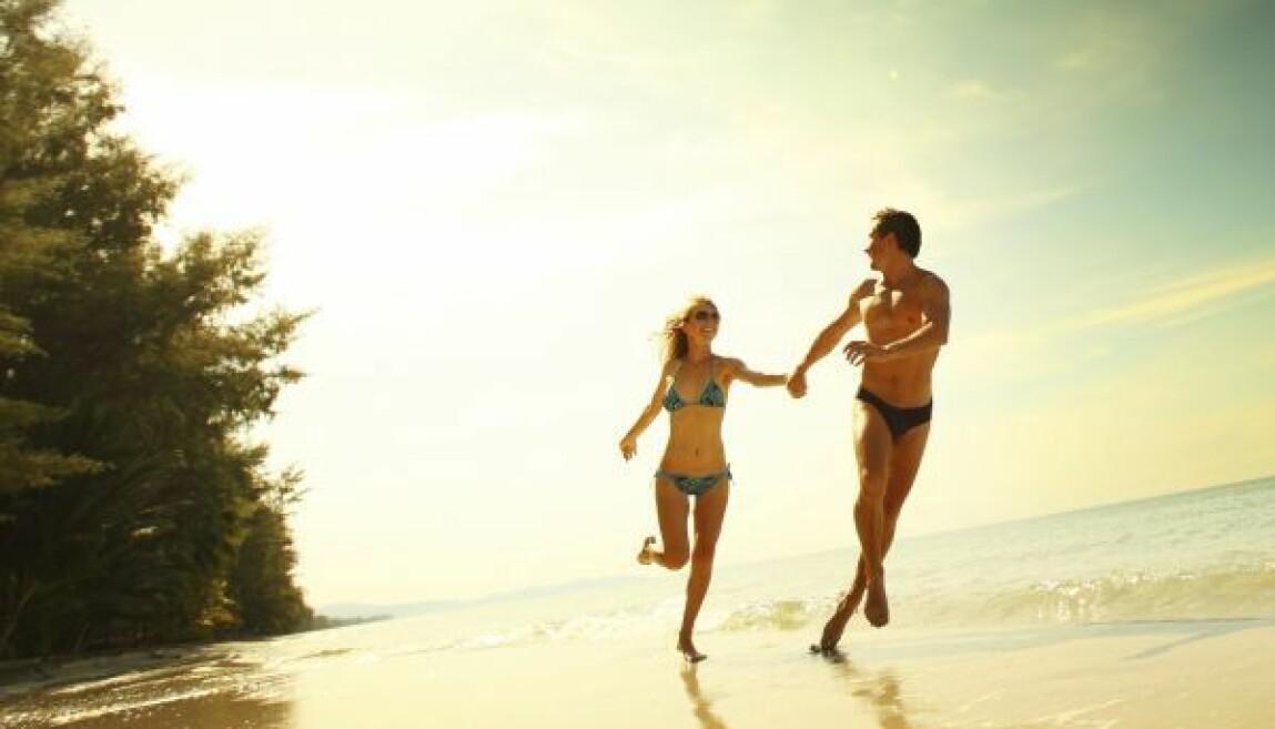 Ett par springer på stranden.