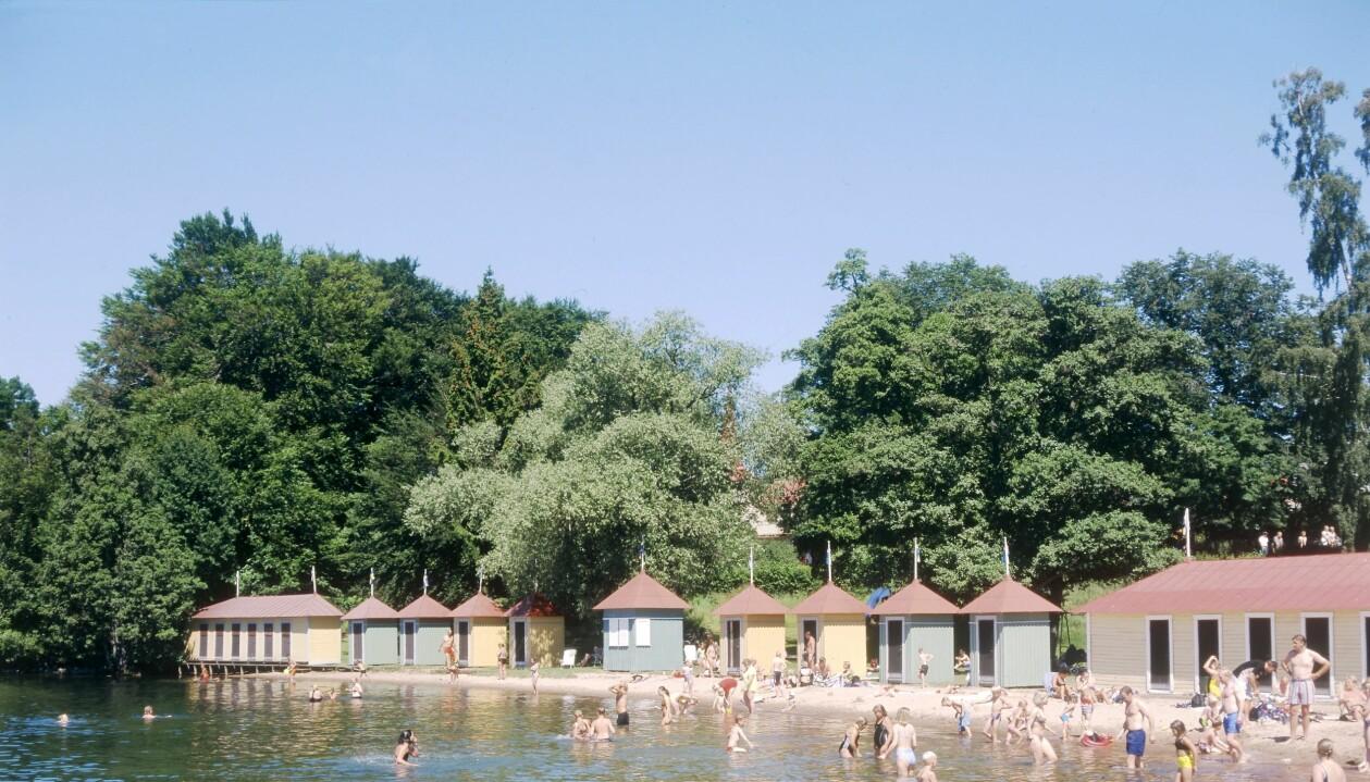 Himlen är blå och gula och gröna badhytter kantar stranden. Flera badsugna personer befinner sig i vattnet.
