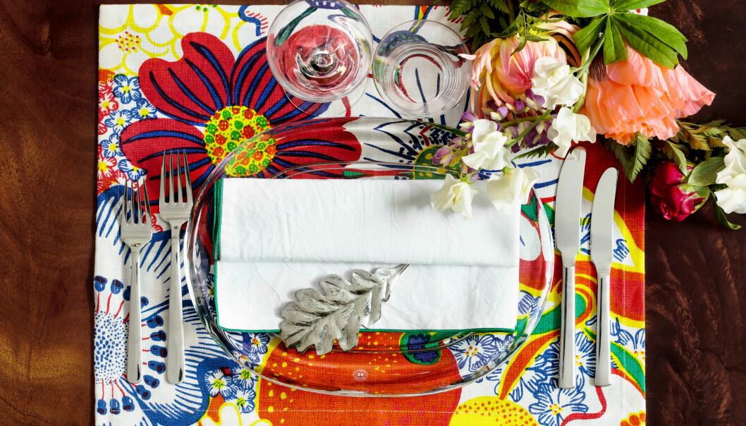 En bordsdukning med Josef Frank tyg, blommor och ett eklöv i silver.