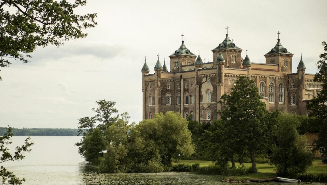 Stora Sundby slott, omgivet av träd och kullar precis intill kanten av Hjälmarens vatten.