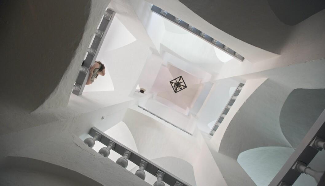 En vindlande trappuppgång i vit puts, fotad nerifrån. En kvinna står lutad mot ett räcke och tittar upp mot taket.