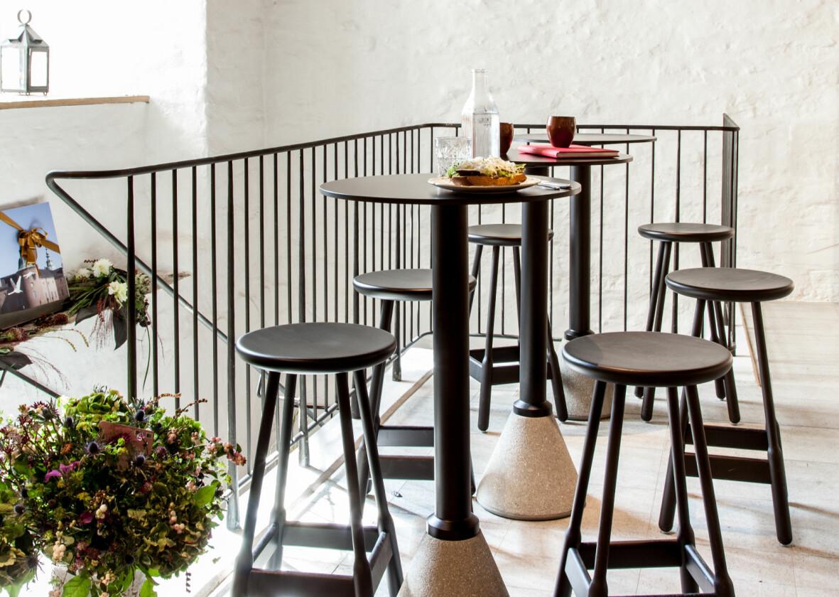 Vita stenväggar, mörka stolar och pallar och ett trappräcke i gjutjärn. På borden står en macka och kaffe. I hörnet skytaren stor bukett blommor.