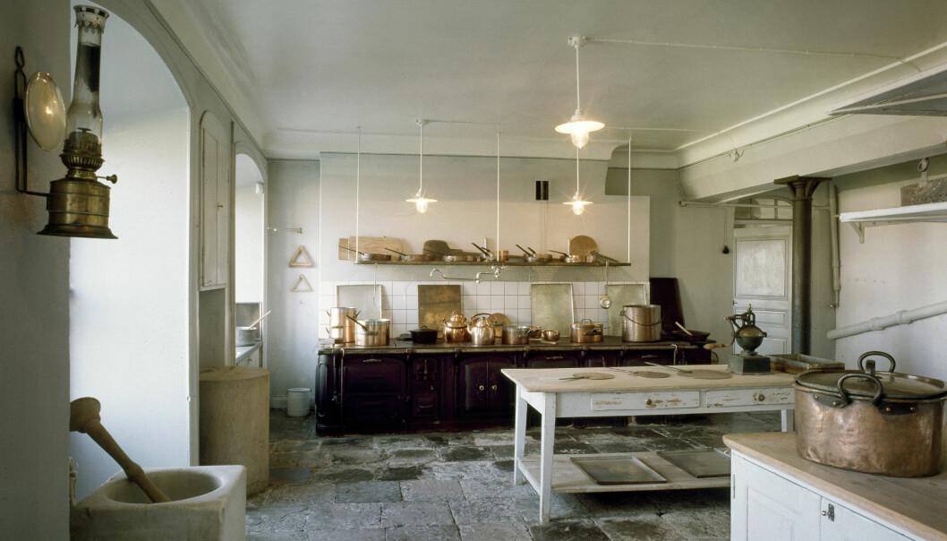 Ett vitt storkök med stengolv. Kastruller och kittlar i koppar täcker arbetsytorna och en morten i marmor står under en fotogenlampett.