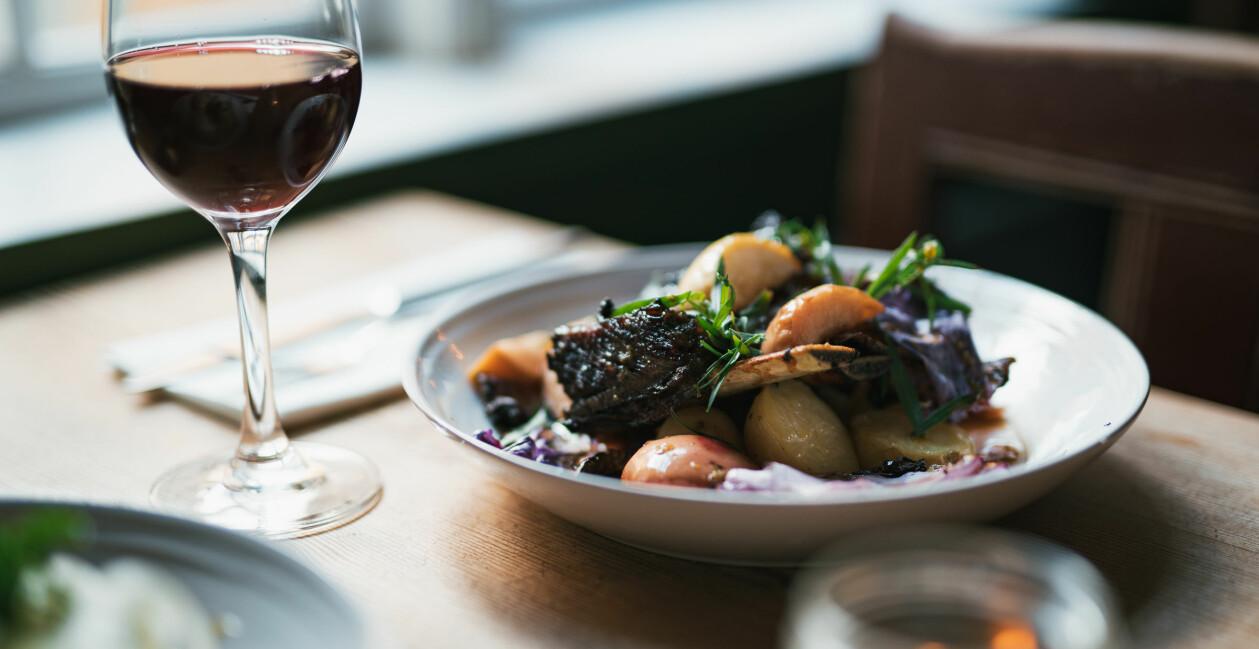 Ett glas rött vin och en tallrik med elegant upplagt kött och grönsaker.