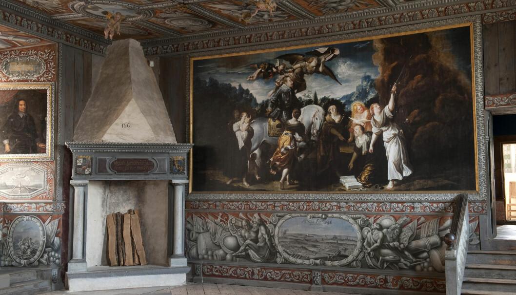 Ett rum i slottet där pampiga målningar täcker väggar och tak. I hörnet står en massiv öppen spis.