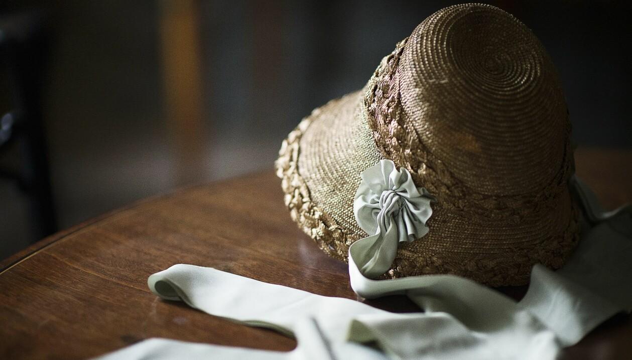 En historisk stråhätta med turkosa sidenband ligger på ett mörkt träbord.