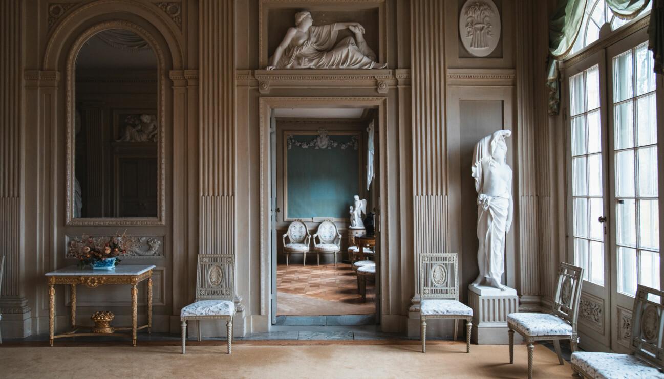 Ett vitt slottsrum med marmorstatyer, ett sirligt avlastningsborg i guld och flera snidade stolar.