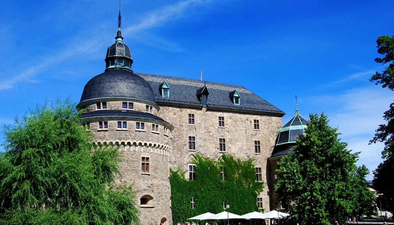 Örebro slott en blå sommardag. Slottet är rustikt i sten och har två kupoler.