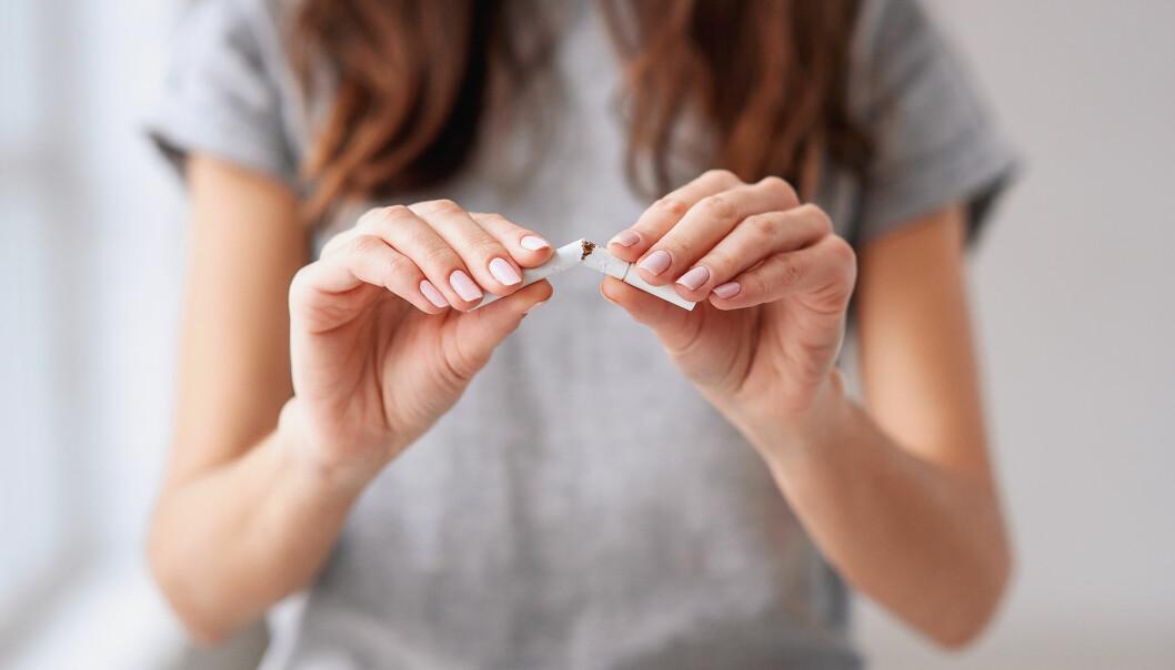 Kvinna bryter en cigarett för att visa att hon slutat röka.