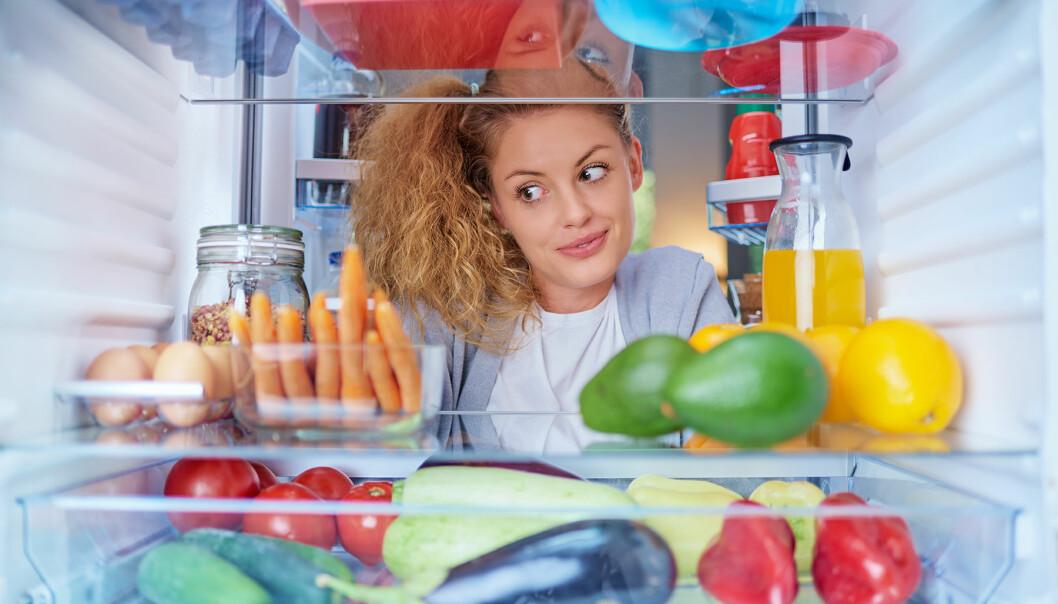 Ung kvinna tittar in ett välfyllt kylskåp.