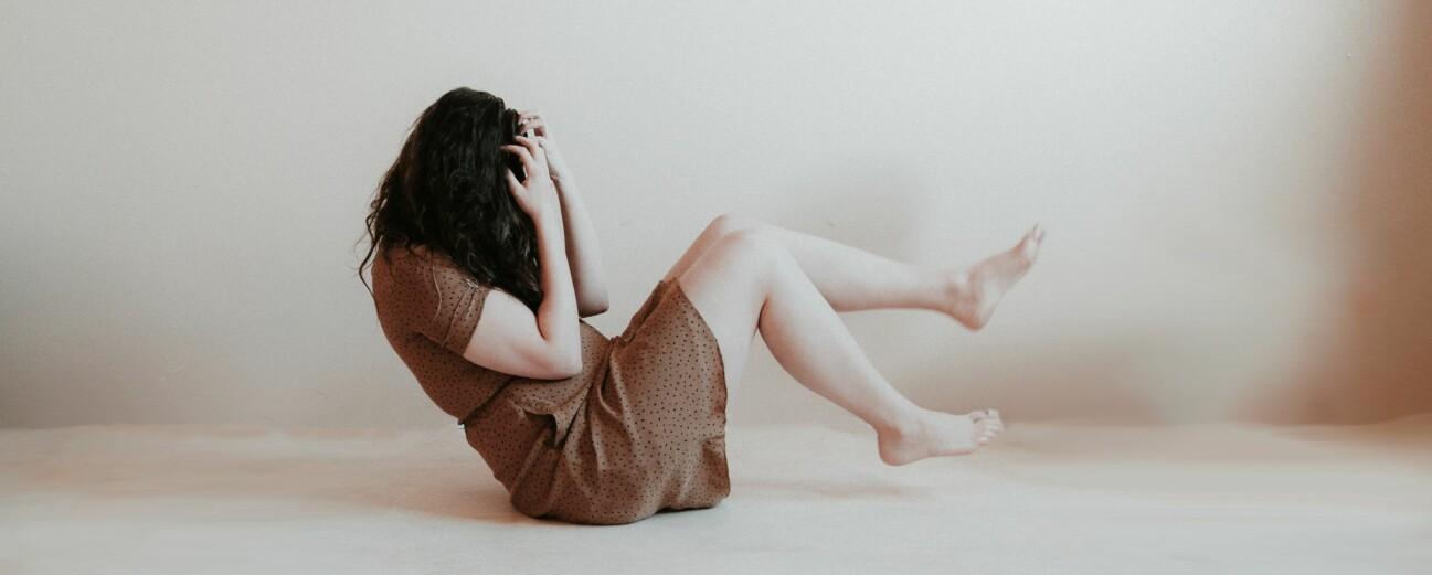En kvinna sitter i ett vitt rum. Hennes händer täcker ansiktet och benen är lyfta som om hon faller fritt.