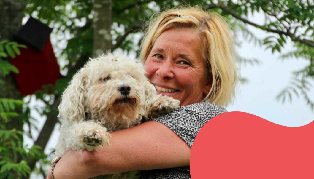 Christina Larsson ler med en vit lurvig hund i famnen