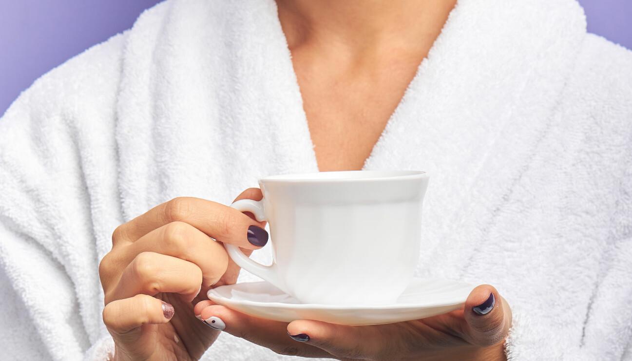 Kvinna i badrock håller i kaffekopp.