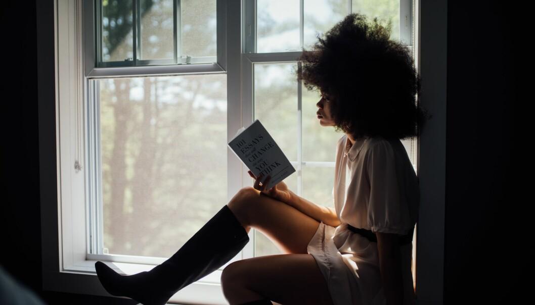 En kvinna läser en pocketbok.