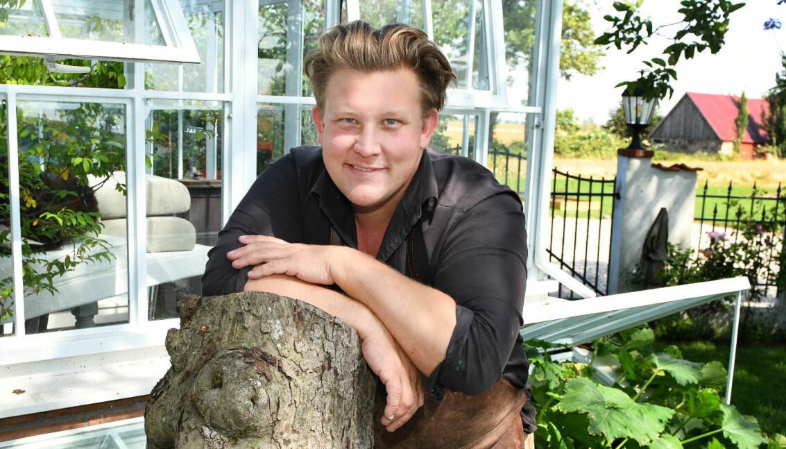 Karl Fredrik på Österlen står i sin trädgård på gården Eklaholm och ler mot kameran.