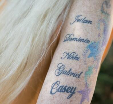Namn tatuerade på överarm på kvinna.